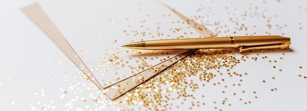 Nota vuota con busta, penna e stelle glitter oro su bianco