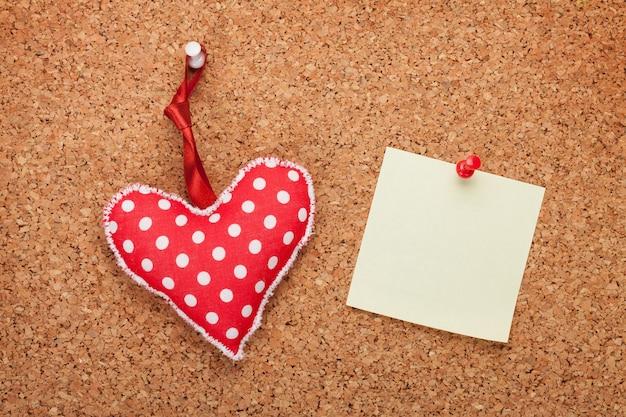 Nota vuota con cuore giocattolo su tavola di sughero in legno