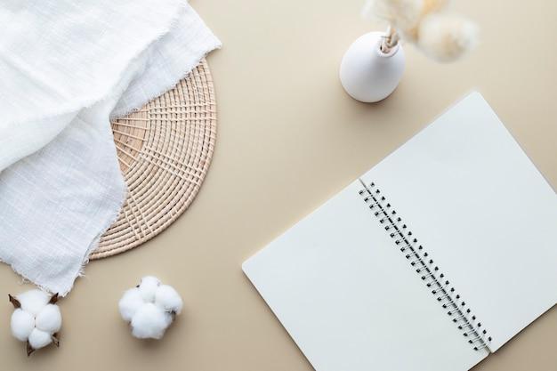 Modello in bianco del taccuino su un fondo beige, fiore di cotone, erba di canne in un vaso, coperta bianca, cestino del rattan, disposizione piana, vista superiore, spazio della copia
