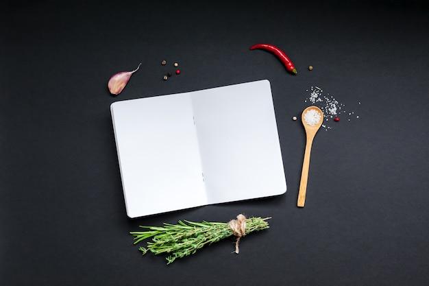 Pagine del taccuino in bianco sulla superficie nera con erbe e spezie verdi