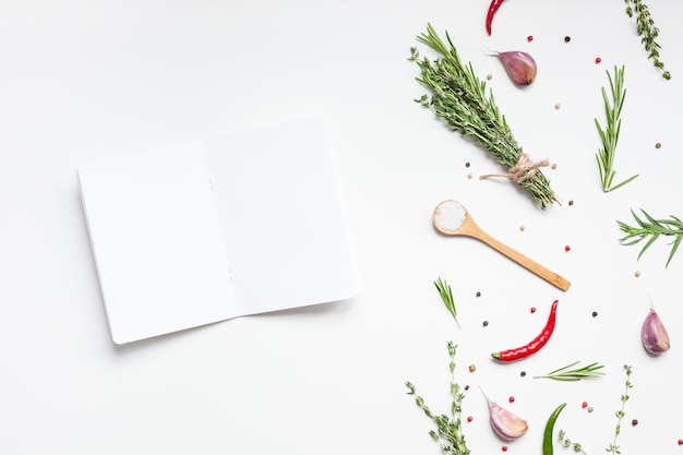 Scheda dell'invito dello spazio del testo del mockup delle pagine del taccuino in bianco su superficie bianca con erbe e spezie verdi