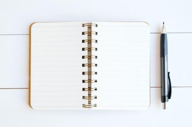 Documento e penna in bianco del taccuino su priorità bassa di legno bianca