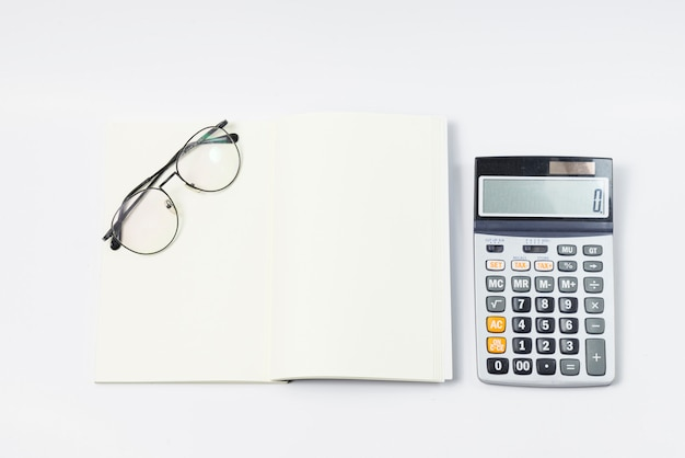 Taccuino in bianco con gli occhiali un taccuino e un calcolatore laterale.