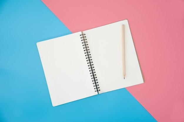 Taccuino in bianco con la matita sul fondo di colore