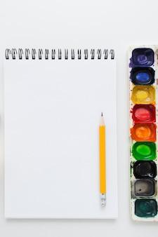Taccuino in bianco con matita e tavolozza dell'acquerello,