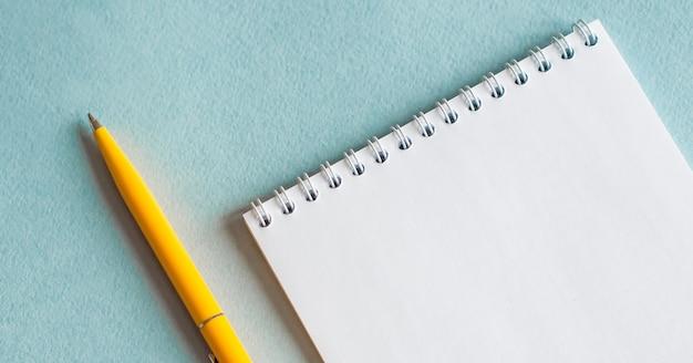 Taccuino in bianco con la tabella blu del penon, concetto di affari