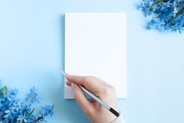Quaderno bianco con fogli bianchi su sfondo azzurro insieme a fiori blu