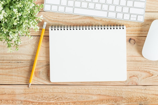 Taccuino in bianco e matita gialla su legno marrone, foto piatta laici del notebook per il tuo messag