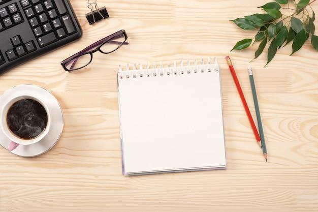 Il blocco note vuoto è in cima al tavolo della scrivania in legno con tastiera, caffè e forniture. lay piatto
