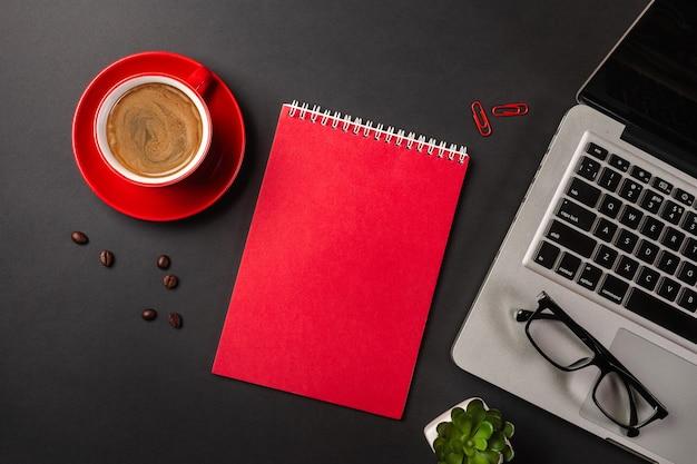 Blocco note in bianco sopra il computer portatile e la tazza di caffè sulla tavola nera dell'ufficio. vista dall'alto con copia spazio.