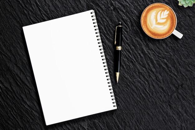 Penna vuota del blocco note sulla scrivania di pietra nera con la tazza di caffè, vista superiore.