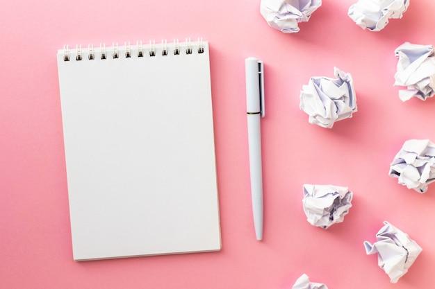 Blocchetto per appunti in bianco, penna e palline di carta sgualcite su colore giallo. scrittura del messaggio. idea nuova o cattiva. lay piatto.