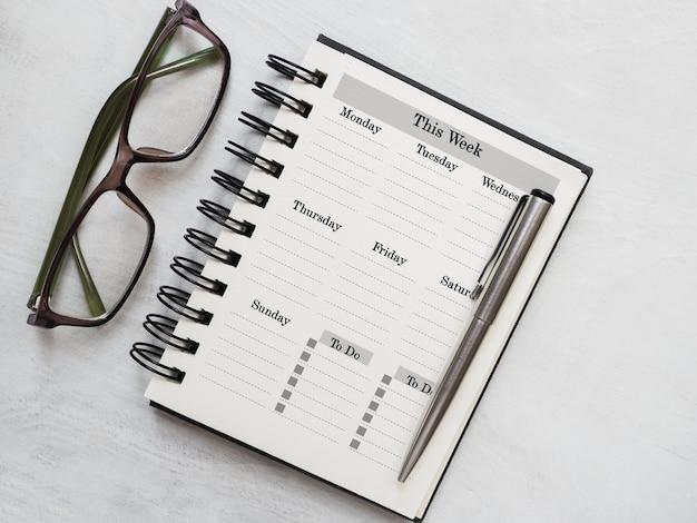 Foglio di blocco note vuoto e calendario per il tuo messaggio di congratulazioni. primo piano, vista dall'alto. nessuno. concetto di preparazione per una vacanza. congratulazioni a parenti, amici e colleghi