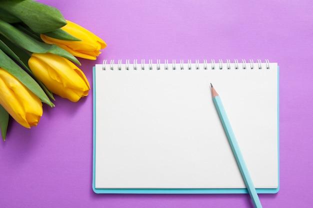 Foglio di blocco note bianco, matita e fiori su uno sfondo viola