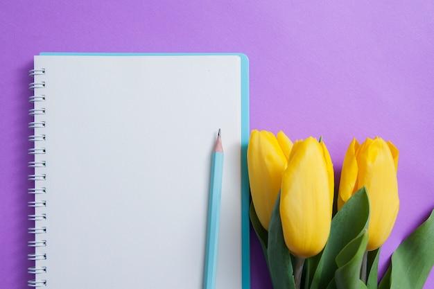 Foglio di blocco note bianco, matita e fiori su una superficie viola