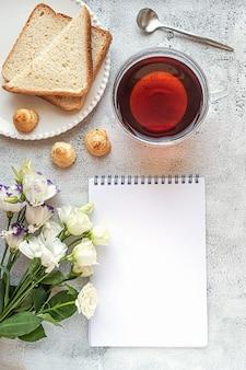Un foglio di blocco note vuoto con impostazione per la colazione e fiori