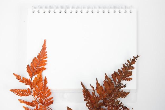 Blocco note vuoto su sfondo bianco decorato con composizione di piante autunnali vista dall'alto piatta