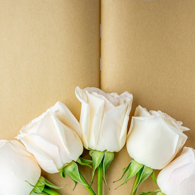 Diario aperto vuoto decorato con rose bianche con spazio per testo o lettere. concetto di scrivere lettere, desideri, obiettivi, piani, storie di vita. composizione piatta primavera mockup