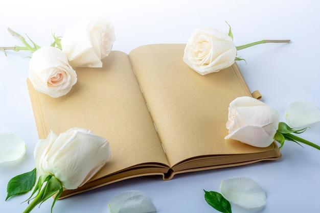 Diario aperto vuoto con rose bianche