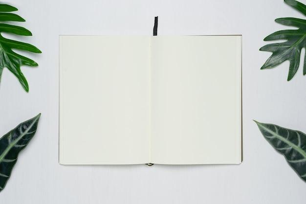 Soppressione la pagina aperta del taccuino sulla scrivania di legno bianca del fondo