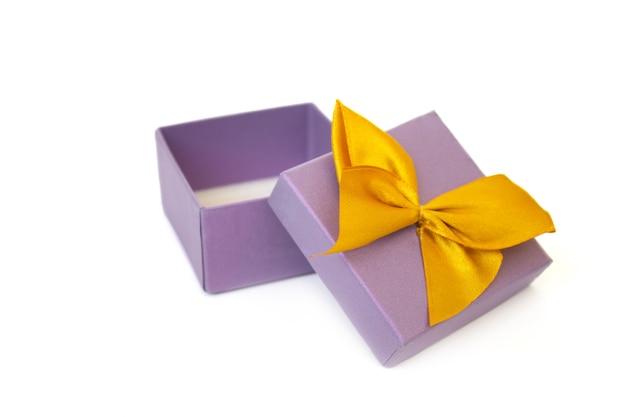 Scatola regalo viola aperta vuota con fiocco in nastro giallo isolato su sfondo bianco