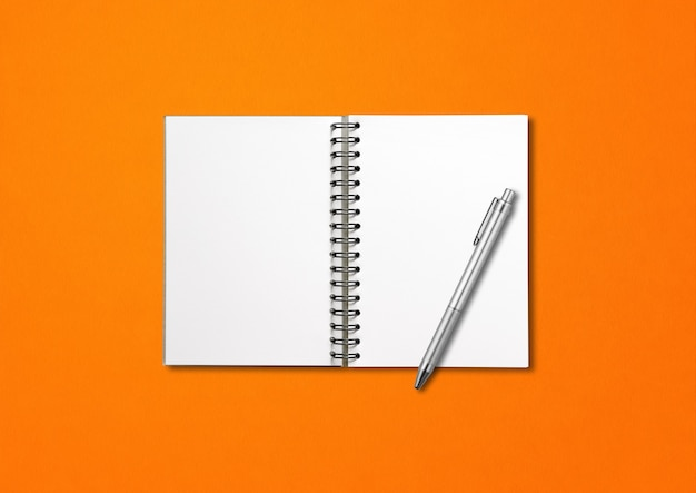 Mockup di taccuino a spirale aperto vuoto e penna isolato su priorità bassa arancione