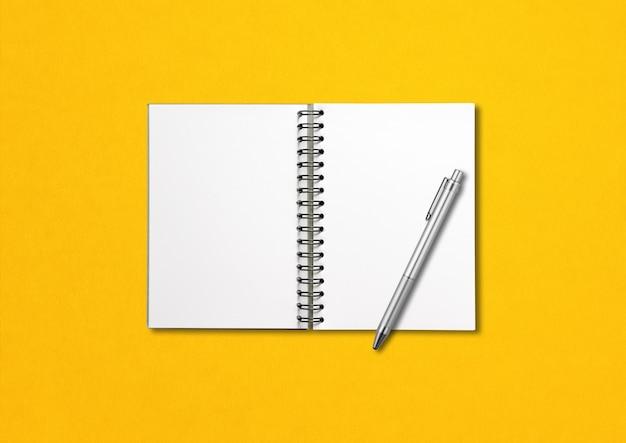 Mockup di taccuino a spirale aperto vuoto e penna isolato su giallo