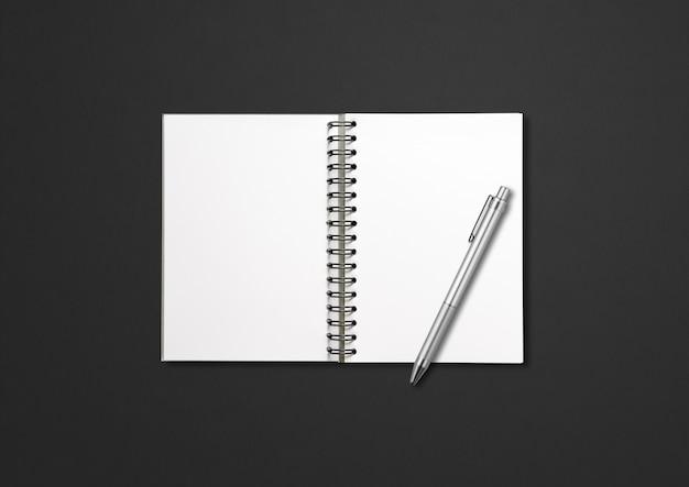 Taccuino a spirale aperto in bianco e penna isolati sul nero
