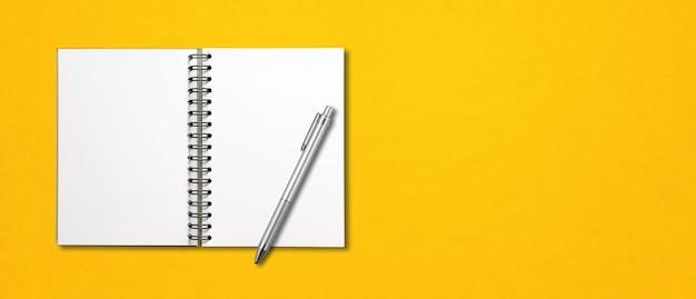 Taccuino a spirale aperto in bianco e penna isolati su colore giallo