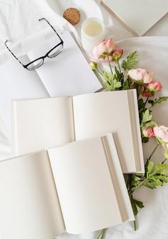 Libri, bicchieri e fiori aperti in bianco sul letto bianco, piatto disteso