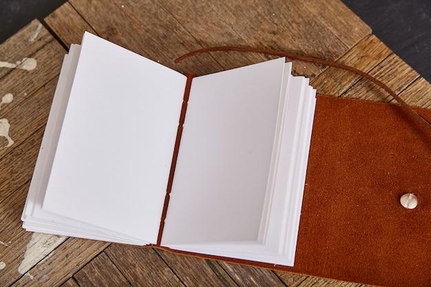 Pagine bianche di diario aperto con pelle marrone su assi di legno