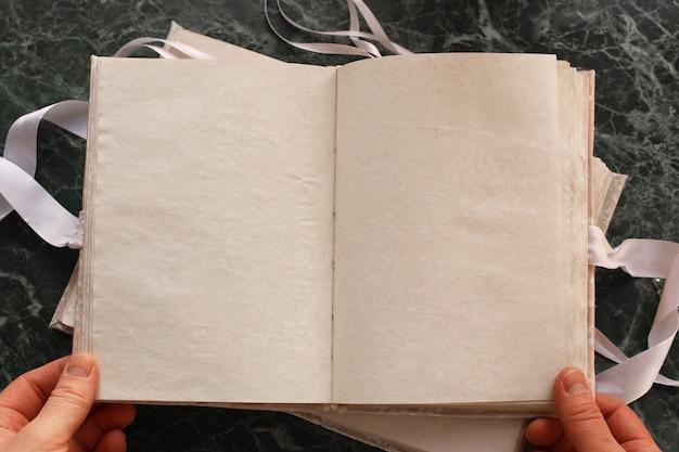Pagine bianche aperte libro vintage su piano di lavoro in marmo verde