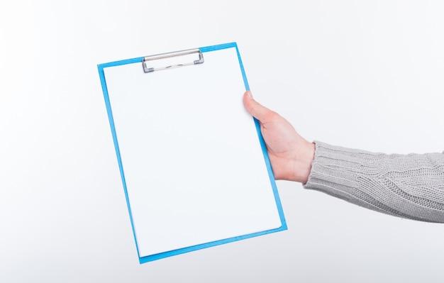 Documento in bianco sul supporto di carta blu tenuto da un uomo su priorità bassa bianca.