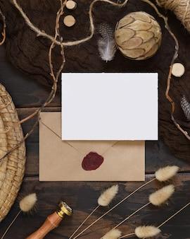 Carta bianca e busta su un tavolo di legno scuro con piante secche intorno, vista dall'alto. scena di mock-up boho con modello di biglietto d'invito