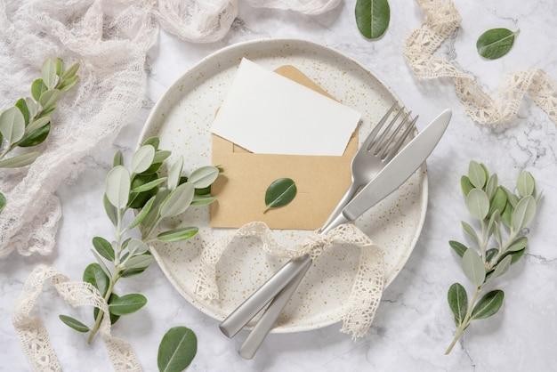 Carta bianca in busta posata su piatto bianco con forchetta e coltello su tavolo di marmo con rami di eucalipto e nastri vintage intorno, vista dall'alto. modello di carta