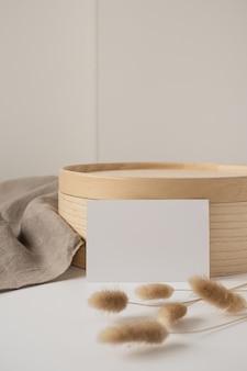 Carta bianca con erba a coda di coniglio, vassoio in legno, coperta beige neutra.