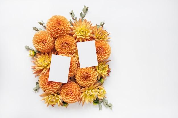 Schede di carta bianche. copia il modello di mockup dello spazio. cornice fatta di bellissimi boccioli di fiori di zenzero dalia e rami di eucalipto