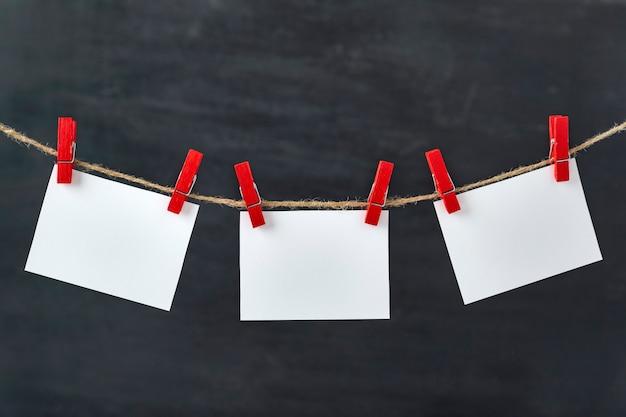 Le carte di carta bianche sono appese con mollette sulla corda. superficie nera. copia spazio.