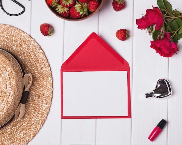 Rose rosse e fragole del cappello della carta in bianco su fondo di legno bianco concetto di estate