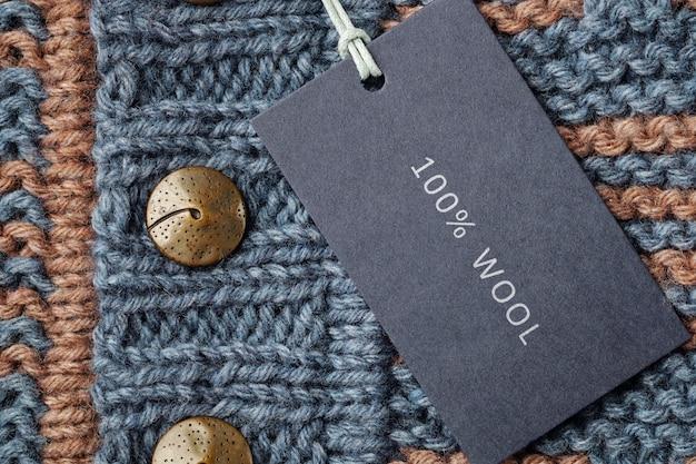 Etichetta o etichetta della carta in bianco sui vestiti tricottati della lana