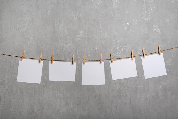 Note di carta bianca appese con mollette sulla corda. superficie grigia. copia spazio.