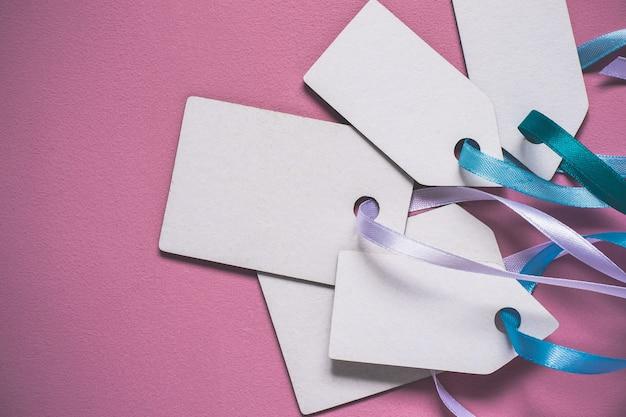 Etichette di vendita di prezzi di carta bianca su sfondo rosa.