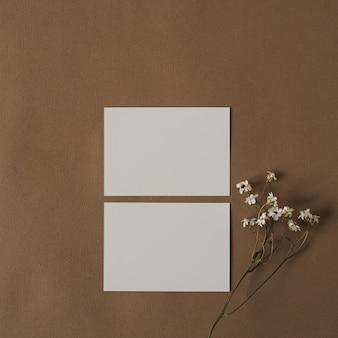 Scheda foglio di carta bianca con bellissimi fiori bianchi. modello di business minimale estetico su marrone beige pastello profondo