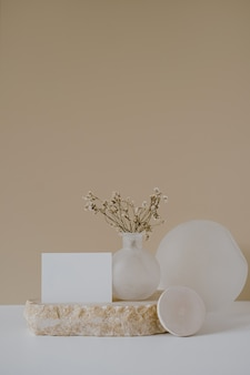 Foglio di carta bianco con fiori su pietra di marmo contro muro beige neutro