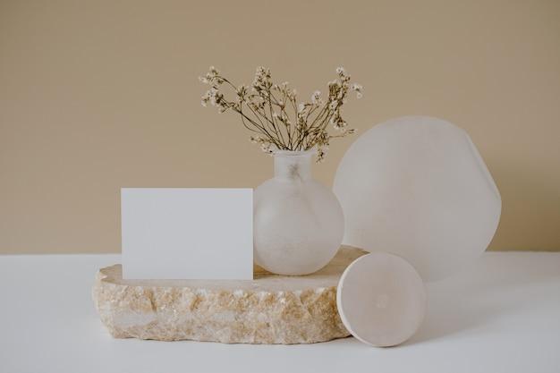 Foglio di carta bianco con spazio copia mockup, fiori secchi, pietra di marmo contro muro beige neutro