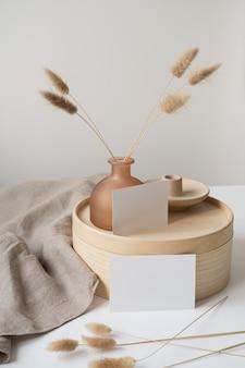 Carte in fogli di carta bianca con erba coda di coniglio, cofanetto in legno e coperta di lino grigio.