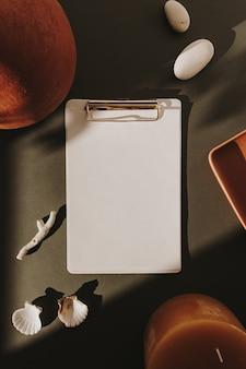 Blocco per appunti in foglio di carta bianco, ombre del sole, pietra, conchiglia, corallo, vaso di terracotta, candela sul verde intenso