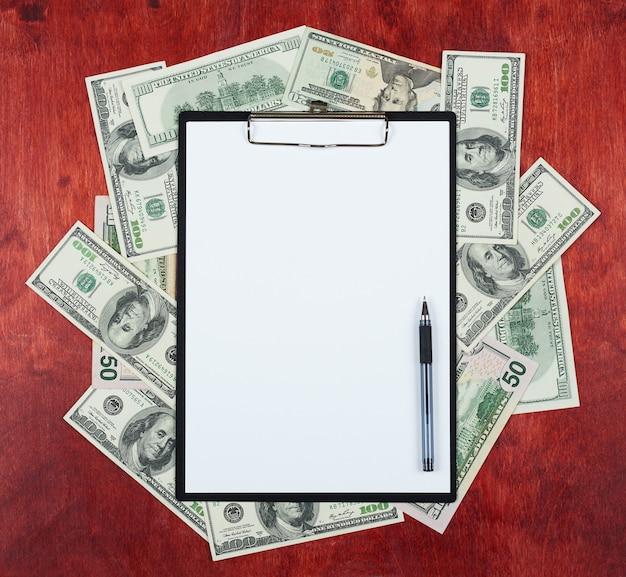 Foglio di carta bianco negli appunti posizionato sul centro del dollaro di denaro e sullo sfondo di legno