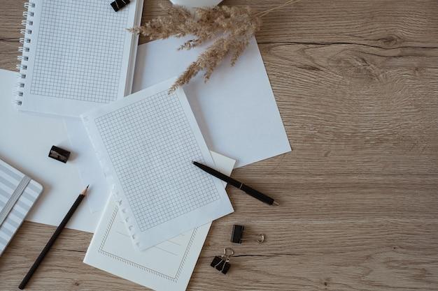Foglio di carta bianco sul tavolo. area di lavoro della scrivania dell'ufficio domestico dell'artista con matita, erba della pampa