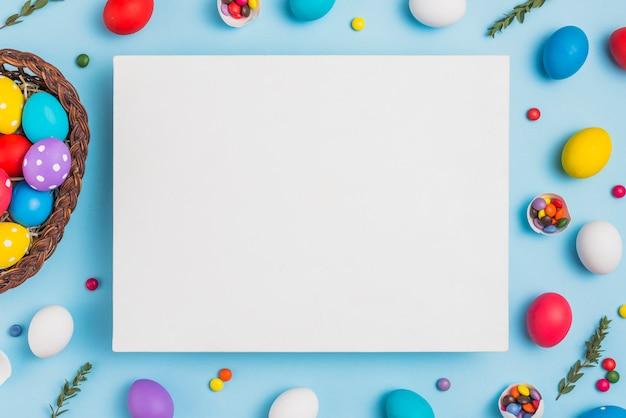 Carta in bianco con la merce nel carrello delle uova di pasqua sulla tavola